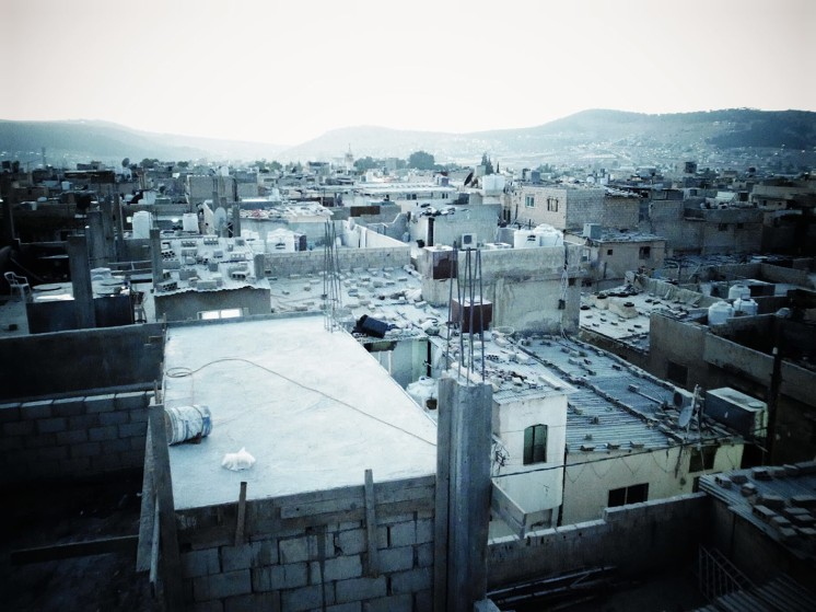 A birds' eye view of Baqa'a camp's (Jordan) density today. Refugees often maintain zinc roofing on their top floors, to be able to expand vertically once means allow. (c) S. Maqusi. 2014.